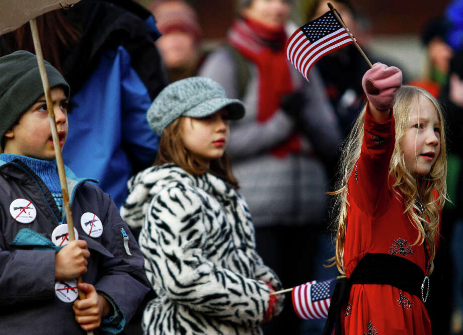 Tallulah Assaf, 6, right, waves a flag during the StandUp Washington March and Rally for Gun Control on Sunday, January 13, 2013 in Seattle. Marchers called for sensible gun control laws in the wake of the tragic shooting at Sandy Hook Elementary School in Connecticut. Photo: NICK ADAMS, FOR SEATTLEPI.COM / SEATTLEPI.COM