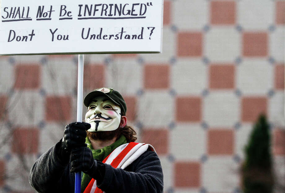 A man who didn't wish to be identify holds up a sign in support of gun rights during the StandUp Washington March and Rally for Gun Control on Sunday, January 13, 2013 in Seattle. Marchers called for sensible gun control laws in the wake of the tragic shooting at Sandy Hook Elementary School in Connecticut. Photo: NICK ADAMS, FOR SEATTLEPI.COM / SEATTLEPI.COM