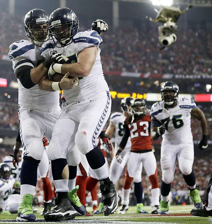 Seattle Seahawks outside linebacker K.J. Wright (50) picks up the ball after Marshawn Lynch scored a touchdown  during the second half of an NFC divisional playoff NFL football game against the Atlanta Falcons Sunday, Jan. 13, 2013, in Atlanta. (AP Photo/David Goldman) Photo: David Goldman, Associated Press