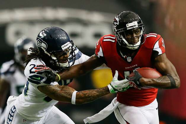 ATLANTA, GA - JANUARY 13:   Julio Jones #11 of the Atlanta Falcons tries to avoid the tackle of  Earl Thomas #29 of the Seattle Seahawks during the NFC Divisional Playoff Game at Georgia Dome on January 13, 2013 in Atlanta, Georgia.  (Photo by Kevin C. Cox/Getty Images) Photo: Kevin C. Cox, Getty Images