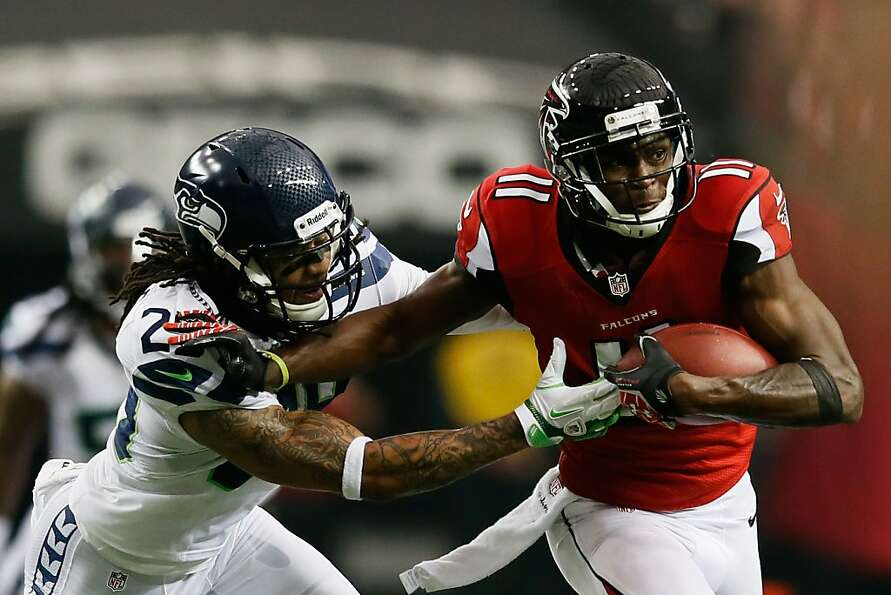 ATLANTA, GA - JANUARY 13:   Julio Jones #11 of the Atlanta Falcons tries to avoid the tackle of  Ear