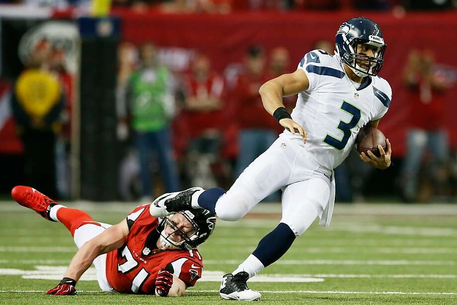 Russell Wilson, a dual threat like Colin Kaepernick, had a combined 445 yards rushing and passing against Atlanta on Sunday. Photo: Kevin C. Cox, Getty Images