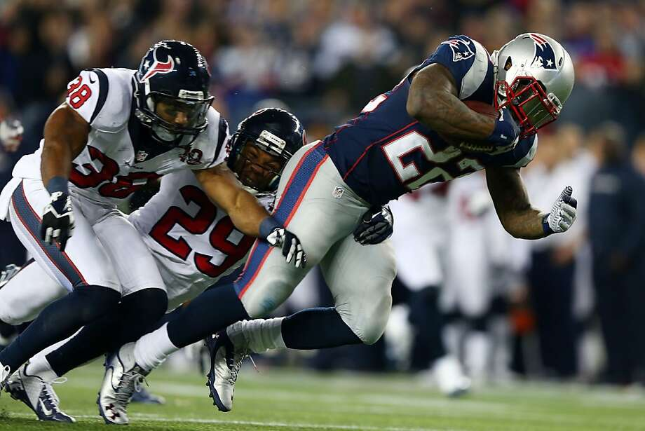 FOXBORO, MA - JANUARY 13:  Stevan Ridley #22 of the New England Patriots runs with the ball against Danieal Manning #38 and Glover Quin #29 of the Houston Texans during the 2013 AFC Divisional Playoffs game at Gillette Stadium on January 13, 2013 in Foxboro, Massachusetts.  (Photo by Elsa/Getty Images) Photo: Elsa, Getty Images