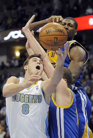 Denver Nuggets forward Danilo Gallinari, left, of Italy, puts up a shot over Golden State Warriors forward David Lee, right, and center Festus Ezeli, top, in the second half of an NBA basketball game on Sunday, Jan. 13, 2013, in Denver. The Nuggets won 116-105. (AP Photo/Chris Schneider) Photo: Chris Schneider, Associated Press