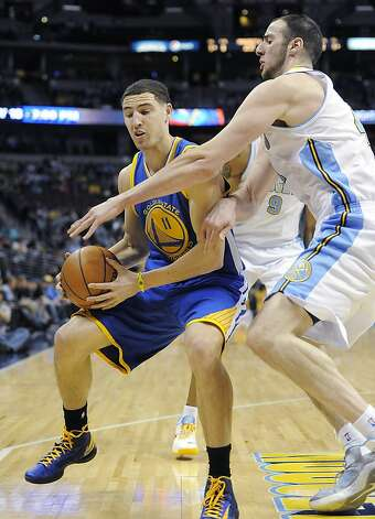 Denver Nuggets center Kosta Koufos, right, defends against Golden State Warriors guard Klay Thompson, left, in the first quarter of an NBA basketball game on Sunday, Jan. 13, 2013, in Denver. The Nuggets won 116-105. (AP Photo/Chris Schneider) Photo: Chris Schneider, Associated Press