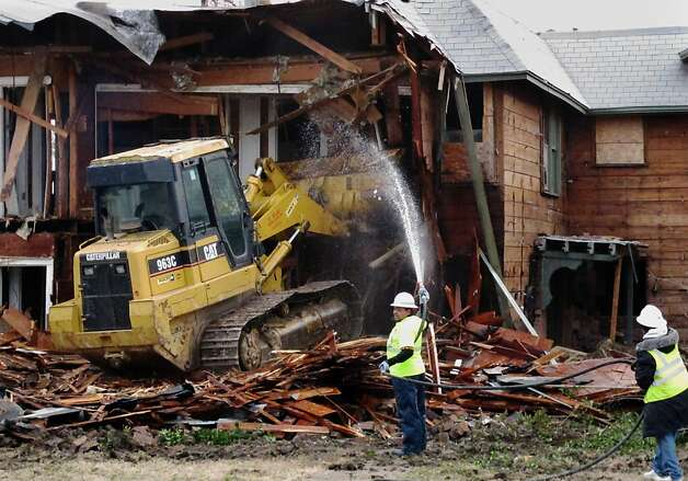 A bulldozer demolishes an apartment building in Dallas where Lee Harvey Oswald briefly lived. Photo: Nomaan Merchant, Associated Press