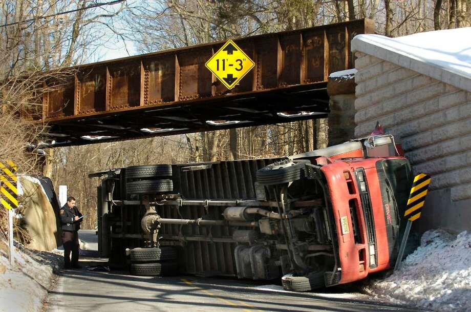 The scene of an accident  in which a truck heading south on Old Stamford Road (Route 106) in New Canaan on Wednesday morning Dec. 23rd, 2009, collided with the railroad bridge above the road.  Local emergency personnel said there were no injuries. Photo: Bob Luckey / Stamford Advocate