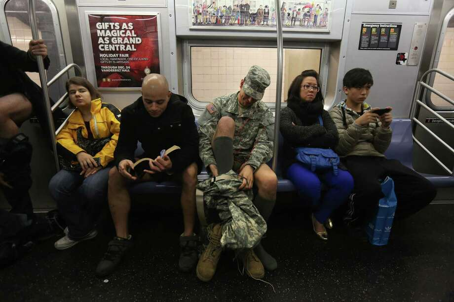 "NEW YORK, NY - JANUARY 13:  A soldier takes off his pants while riding the subway on January 13, 2013 in New York City. He and thousands of others participated in the 12th annual No Pants Subway Ride, organized by New York City prank collective Improv Everywhere. During the afternoon event, participants boarded separate subway stops and removed their pants, pretending that they did not know each other. The event, refered to as a ""celebration of silliness"" is designed to make fellow subway riders laugh and smile. Photo: John Moore, Getty Images / 2013 Getty Images"