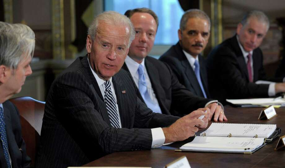 Vice President Joe Biden, second from left, with Attorney General Eric Holder, second from right, speaks during a meeting with representatives from the video game industry in the Eisenhower Executive Office Building on the White House complex in Washington, Friday, Jan. 11, 2013. Biden is holding a series of meetings this week as part of the effort he is leading to develop policy proposals in response to the Newtown, Conn., school shooting. Entertainment Software Association President Mike Gallagher sits between Biden and Holder.  (AP Photo/Susan Walsh) Photo: Susan Walsh, Associated Press / AP