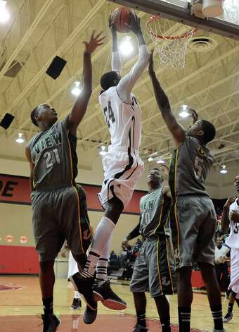 Central player E'Torrion Wilridge, #24, puts it up for two during the Central High School Jaguars basketball game against Long View High School on Thursday, December 27, 2012, at the James Gamble Boys Basketball Tournament held at Port Arthur Memorial High School. Central won over Long View 67 - 64. Photo taken: Randy Edwards/The Enterprise