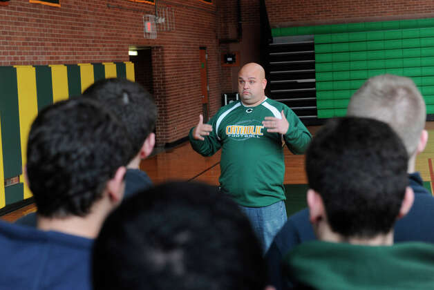 Donny Panapada addresses the Trinity Catholic football team Monday for the first time as head coach. Photo: Helen Neafsey / Greenwich Time