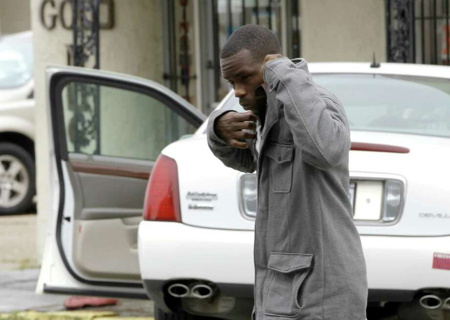 Cedric Deray Scott reaches to cover his face in from cameras outside the Liberty County Courthouse before a status update in his case Monday, Dec. 5, 2011, in Liberty. (AP Photo/David J. Phillip) Photo: David J. Phillip, Associated Press / AP