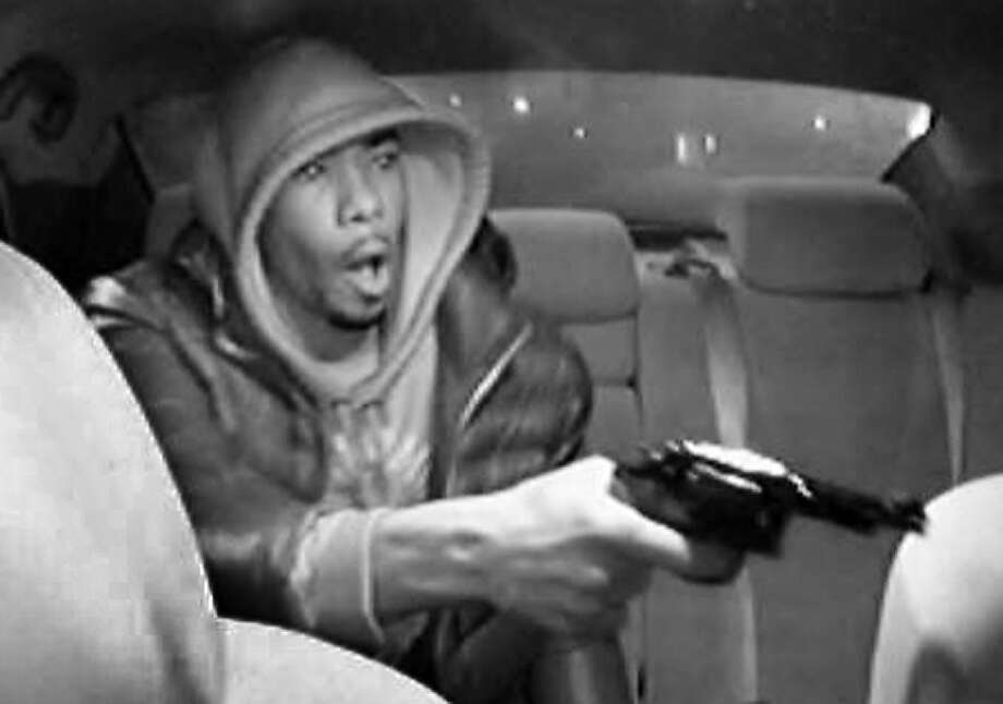 Taxi cam captures armed robbery: In this video frame grab provided by the New York Police Department, an unidentified gunman points a pistol at a livery car driver (not shown) in New York. Police say the gunman entered the cab, displayed the firearm and demanded money. He then fired three shots at the driver, Raphael Martinez, who was later hospitalized in stable condition. The photo was made by a security camera mounted in the cab. Photo: Associated Press