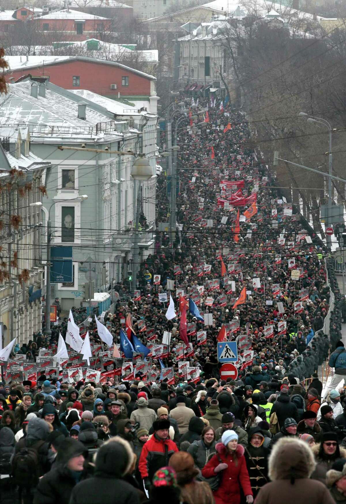 People march during a protest rally in Moscow, Russia, on Sunday. Thousands of people are gathering in central Moscow to protest against Russia's new law banning Americans from adopting Russian children. They carry posters of President Vladimir Putin and members of Russia's parliament who overwhelmingly voted for the law last month. The posters have the word