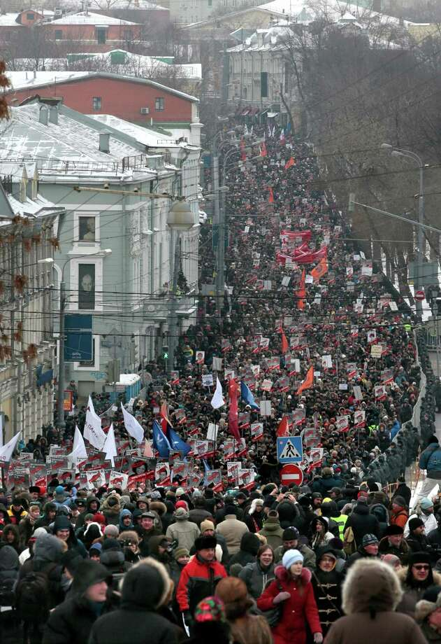 "People march during a protest rally in Moscow, Russia, on Sunday. Thousands of people are gathering in central Moscow to protest against Russia's new law banning Americans from adopting Russian children. They carry posters of President Vladimir Putin and members of Russia's parliament who overwhelmingly voted for the law last month. The posters have the word ""Shame"" written in red over the faces and proclaim that Sunday's demonstration is a ""March Against the Scum"" who enacted the law. Photo: AP"