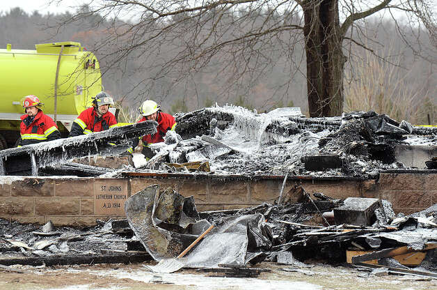 Members of the Colfax, Wis. Fire Department examine charred remains Sunday of St. John's Lutheran Church in the Town of Grant, Dunn County, Wis. A fire late Saturday, Jan. 12 destroyed the nearly 100-year-old rural church located about 10 miles north of Colfax. Photo: AP