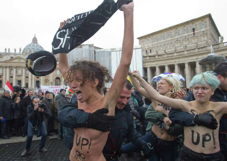 "Italian police officers stop members of a group of four women who went topless to protest the Vatican's opposition to gay marriage, in St. Peter's Square at the Vatican on Sunday. Police quickly took the women away, and the pope appeared not to have been disturbed as he delivered his traditional prayer from his studio window overlooking the piazza. On their bare backs, the women had painted slogans ""In Gay We Trust,"" and ""Shut Up. Photo: AP"