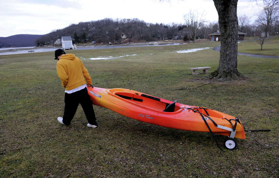 Kevin Dinho, 30, of Danbury, carries his Kayak to the water at the Danbury Candlewood Park, to take advantage of the melted ice on the lake, Monday, January 14, 2013. Photo: Carol Kaliff / The News-Times