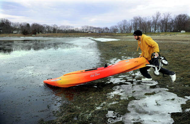 Kevin Dinho, 30, of Danbury, launches his Kayak into the water at the Danbury Candlewood Park, to take advantage of the mild temperature and melted ice on the lake, Monday, January 14, 2013. Photo: Carol Kaliff / The News-Times