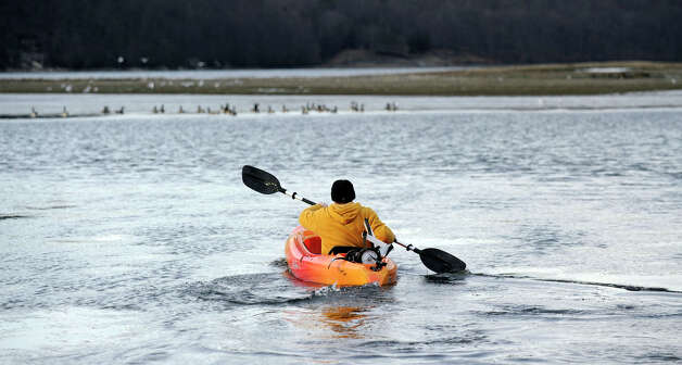 "Kevin Dinho, 30, of Danbury, heads his kayak to the sand bars off the beach at the Danbury Candlewood Park Monday, January 14, 2013.  He says he is taking advantage of the ""beautiful day"" and low water levels to explore area. Photo: Carol Kaliff / The News-Times"