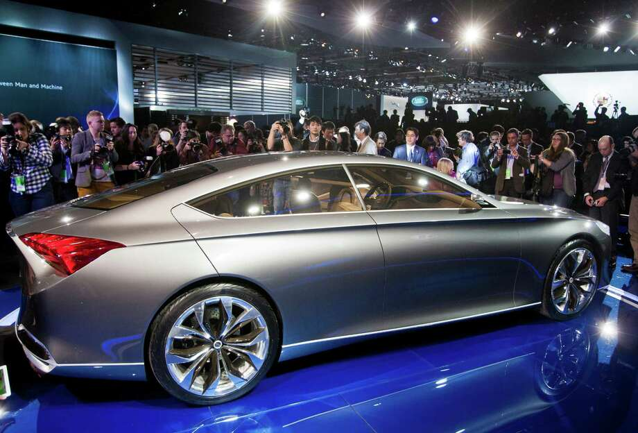 Journalists and photographers crowd around the Hyundai Genesis HCD-14 concept car, at the North American International Auto Show, Monday, Jan. 14, 2013, in Detroit, Mich. (AP Photo/Tony Ding) Photo: TONY DING, Associated Press / FR143848 AP