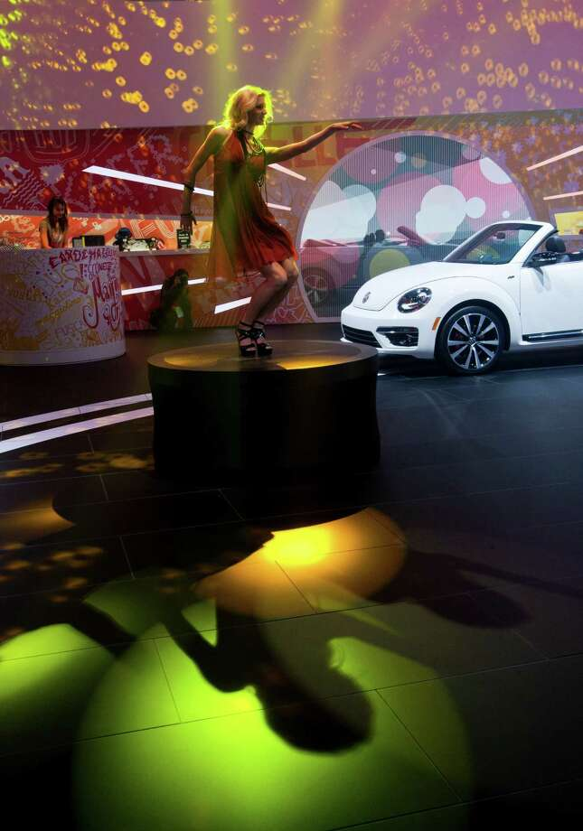 A woman dances to music on a pedestal at the Volkswagen display, at the North American International Auto Show, Monday, Jan. 14, 2013, in Detroit, Mich. (AP Photo/Tony Ding) Photo: TONY DING, Associated Press / FR143848 AP