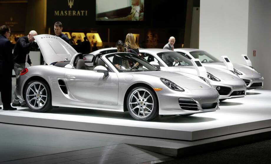Journalists look over a Porsche Boxster during the North American International Auto Show in Detroit, Monday, Jan. 14, 2013. (AP Photo/Carlos Osorio) Photo: Carlos Osorio, Associated Press / AP