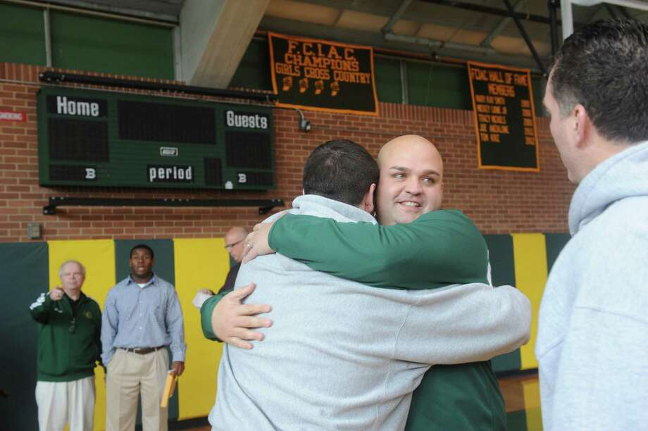 Donny Panapada, the new football coach, gets a hug from Riley Kinahan, 17, a senior, at Trinity Catholic High School in Stamford, Conn., Monday, Jan. 14, 2013. Photo: Helen Neafsey / Greenwich Time
