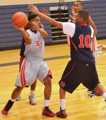 Hardin-Jefferson boys basketball player Devante Johnson, left, looks to pass off the ball towards the basket during Monday's January 14, 2013 athletic period.   Johnson is a senior and has helped led the team offensively this season.  Dave Ryan/The Enterprise Photo: Dave Ryan