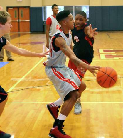 Hardin-Jefferson boys basketball player Devante Johnson, middle, looks to pass off the ball towards the basket during Monday's January 14, 2013 athletic period.   Johnson is a senior and has helped led the team offensively this season.  Dave Ryan/The Enterprise Photo: Dave Ryan