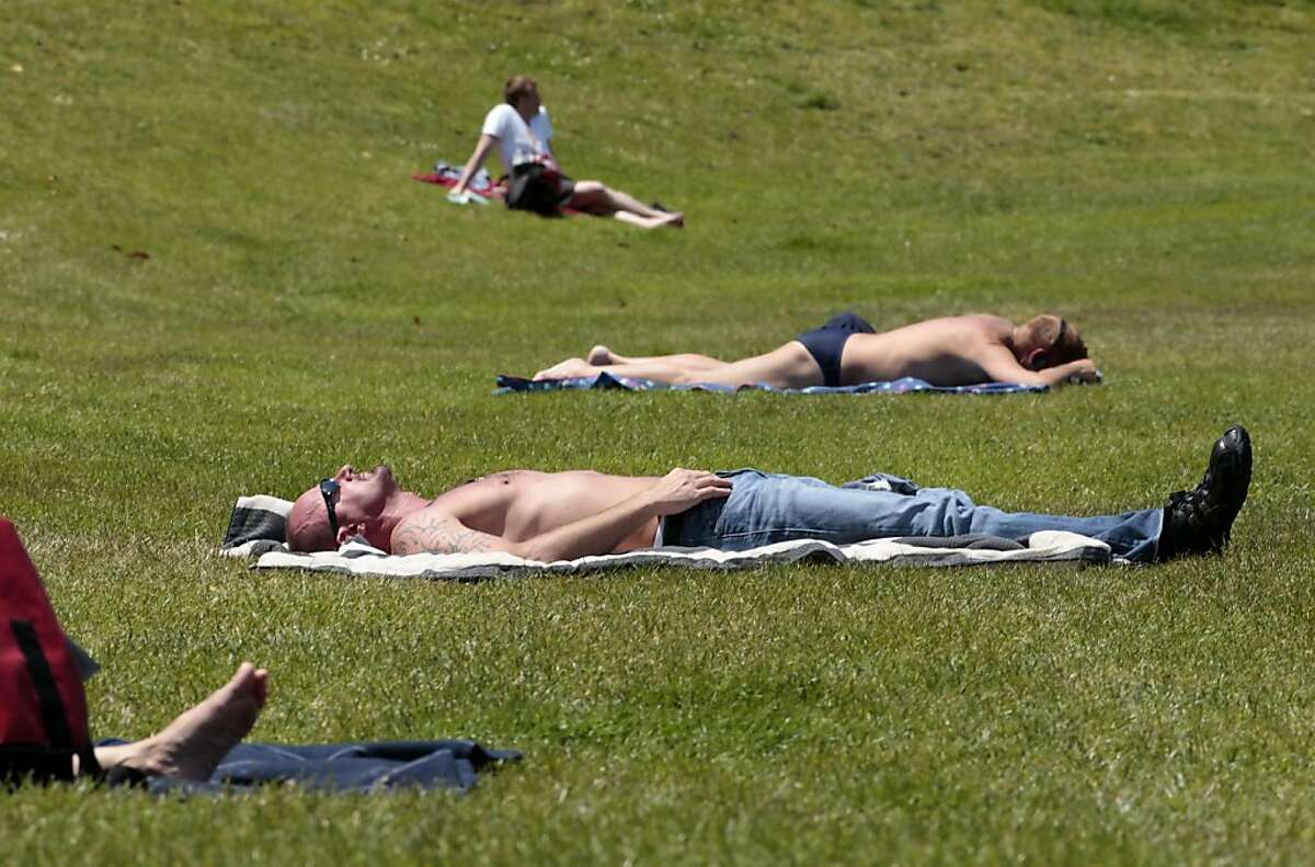 Chris Love, center, who is visiting from Los Angeles, tries to get a little color as he lays out in the sun at Dolores Park , Tuesday May 24, 2011, in San Francisco, Calif. The Environmental Working Group has released its yearly guide to safe sunscreens before the Memorial Day weekend.
