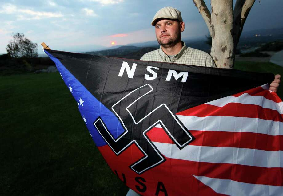 FILE - In this Oct. 22, 2010 file photo, Jeff Hall, who was killed by his son, holds a Neo Nazi flag while standing at Sycamore Highlands Park near his home in Riverside, Calif. Defense attorneys for a boy charged with killing Hall, his neo-Nazi father when he was 10 years old has rested its case without calling the boy to testify, Wednesday, Jan. 9, 2013. (AP Photo/Sandy Huffaker, File) Photo: Sandy Huffaker