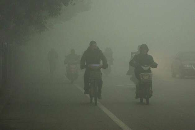 Cyclists travel on the road on a hazy day in Huaibei, in central China's Anhui province Monday Jan. 14, 2013. Air pollution is a major problem in China due to the country's rapid pace of industrialization, reliance on coal power, explosive growth in car ownership and disregard for environmental laws. (AP Photo)  CHINA OUT