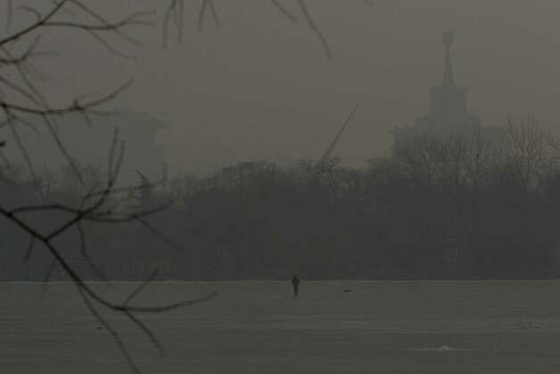 A man walks on an frozen lake on a hazy day in Beijing, China, Monday, Jan. 14, 2013. Beijing schools kept children indoors and hospitals saw a spike in respiratory cases Monday following a weekend of off-the charts pollution in China's smoggy capital, the worst since the government began being more open about air-quality data. (AP Photo/Alexander F. Yuan) Photo: Alexander F. Yuan