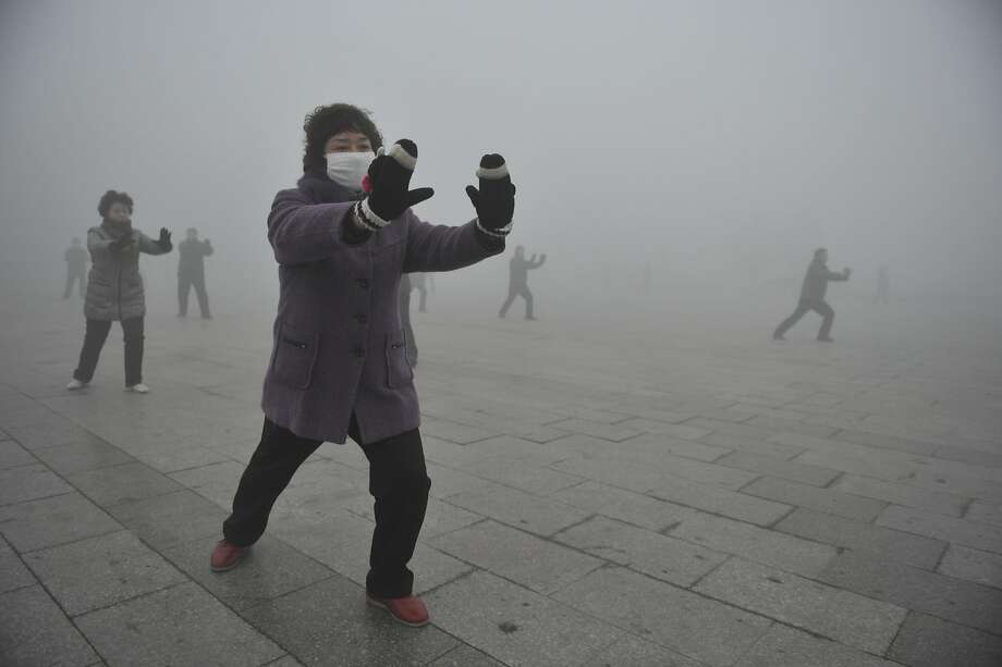 Retirees play Taichi during their morning exercise on a hazy day in Fuyang city, in central China's Anhui province, Monday Jan. 14, 2013. Air pollution is a major problem in China due to the country's rapid pace of industrialization, reliance on coal power, explosive growth in car ownership and disregard for environmental laws. (AP Photo)  CHINA OUT Photo: Associated Press