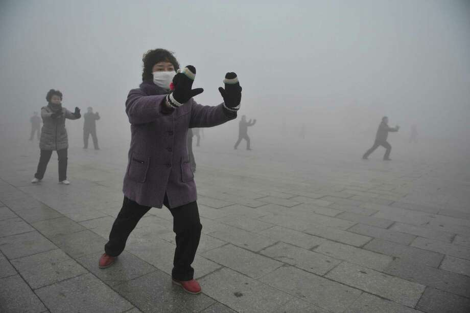 Retirees practice tai chi during their morning exercise Monday in hazy Fuyang, in central China's Anhui province. China's state-run media were remarkably critical about the air pollution problem. Photo: STR / CHINATOPIX