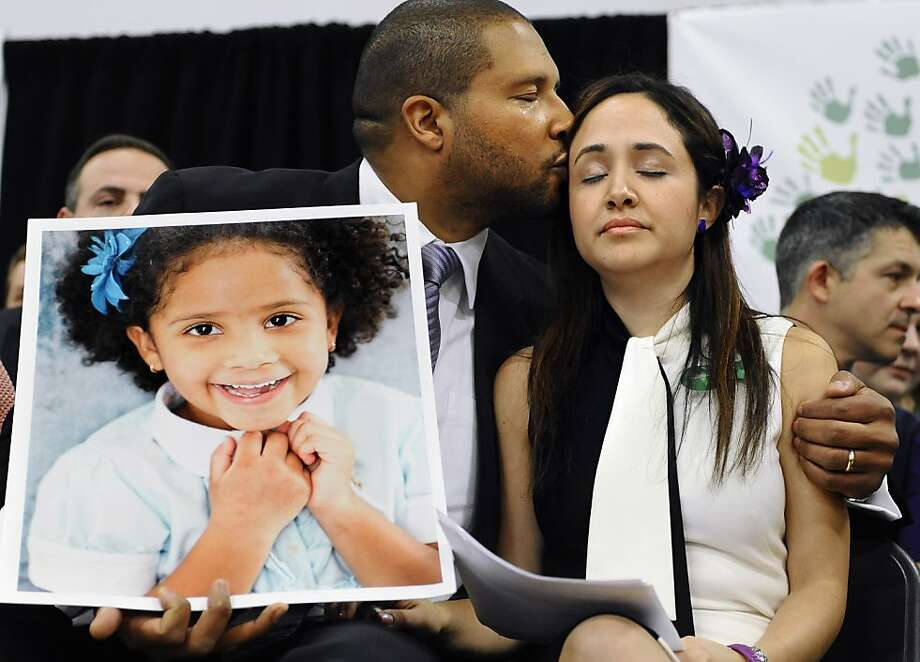 Jimmy Greene kisses his wife, Nelba Marquez-Greene, as he holds a portrait of their daughter, Ana Marquez-Greene, a victim in the Newtown shooting, during a news conference. Photo: Jessica Hill, Associated Press