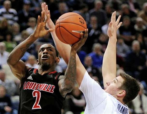 Louisville's Russ Smith (2) drives to the basket past UConn's Tyler Olander during the first half of an NCAA college basketball game  in Hartford, Conn., Monday, Jan. 14, 2013. (AP Photo/Fred Beckham)