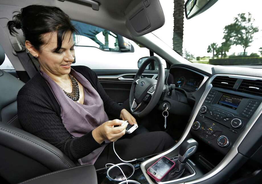 """In this Tuesday, Dec. 18, 2012, photo, Gigi Swanson, Digital Alliances and Partnerships Strategist for Cox Target Media Inc., owner of Valpak, checks coupons through the phone application """"Roximity"""" and Ford's SYNC,  in St. Petersburg, Fla. Valpak has partnered with Roximity, a Denver-based app developer, to bring coupons and deals to drivers of newer-model Fords and Lincolns who use the voice-controlled Sync AppLink connected to their mobile phone. (AP Photo/Chris O'Meara) Photo: Chris O'Meara"""