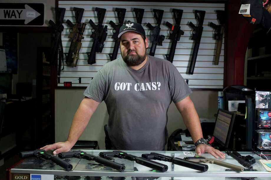 Cris Parsons poses for a photo with various weapons for sale at Houston Armory Tuesday, Jan. 8, 2013, in Stafford. Houston Armory buys an sells, as well as manufactures weapons permitted and strictly controlled by the U.S. government, including machine guns, silencers and other specialty items. Photo: Brett Coomer, Houston Chronicle / © 2013 Houston Chronicle