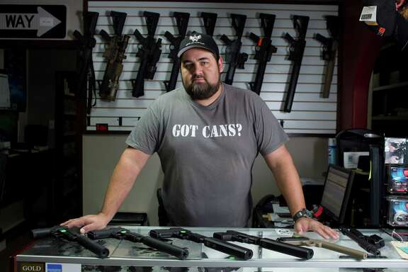Cris Parsons poses for a photo with various weapons for sale at Houston Armory Tuesday, Jan. 8, 2013, in Stafford. Houston Armory buys an sells, as well as manufactures weapons permitted and strictly controlled by the U.S. government, including machine guns, silencers and other specialty items.