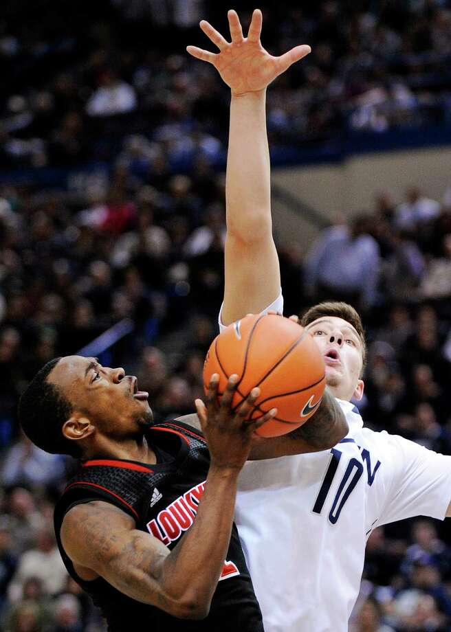 Louisville's Russ Smith, left, drives past Connecticut's Tyler Olander during the second half of an NCAA college basketball game in Hartford, Conn., Monday, Jan. 14, 2013. Smith scored a game-high 23 points in his team's 73-58 victory. (AP Photo/Fred Beckham) Photo: Fred Beckham, Associated Press / FR153656 AP