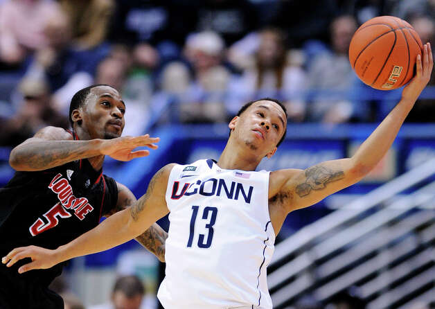 Louisville's Kevin Ware, left, and Connecticut's Shabazz Napier scramble for a loose ball during the second half their NCAA college basketball game in Hartford, Conn., Monday, Jan. 14, 2013. Louisville won 73-58. (AP Photo/Fred Beckham) Photo: Fred Beckham, Associated Press / FR153656 AP
