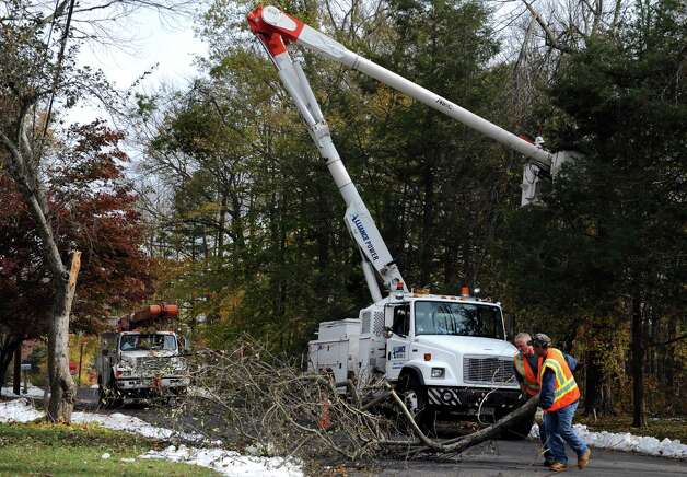 Monroe Public Works employees Chris Corso, left, and Domenick Ciocca clear a tree limb from Harvester Road as workers from Indiana and Michigan trim trees around power lines Thursday, Nov. 3, 2011 in Monroe, Conn. Photo: Autumn Driscoll / Connecticut Post