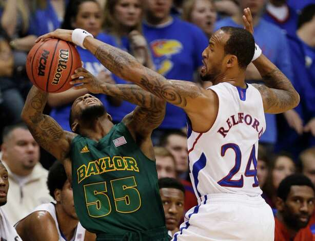 Kansas guard Travis Releford (24) knocks the ball away from Baylor guard Pierre Jackson (55) during the first half of an NCAA college basketball game in Lawrence, Kan., Monday, Jan. 14, 2013. (AP Photo/Orlin Wagner) Photo: Orlin Wagner, Associated Press / AP