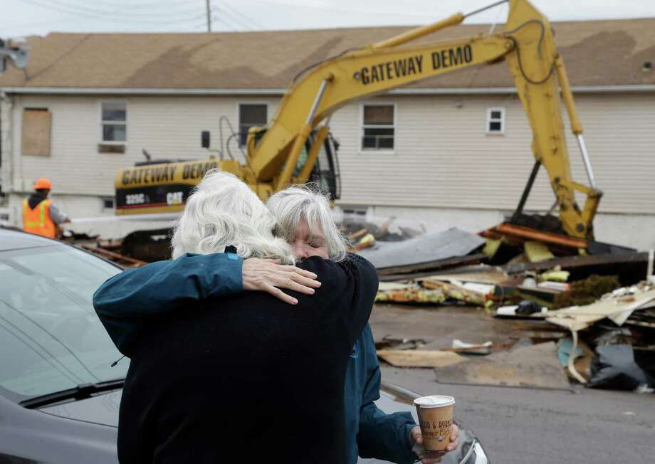Mickey Merrell, right, hugs her sister Ronnie Loesch after watching their childhood home, which was severely damaged during Superstorm Sandy, demolished in Staten Island, New York, Monday, Jan. 14, 2013. Several Staten Island homes damaged beyond repair by Superstorm Sandy are being demolished. Some homeowners called in bulldozers on their own to remove shattered homes in the 11 weeks since the storm. But the first city-facilitated demolitions started Monday. (AP Photo/Seth Wenig) Photo: Seth Wenig