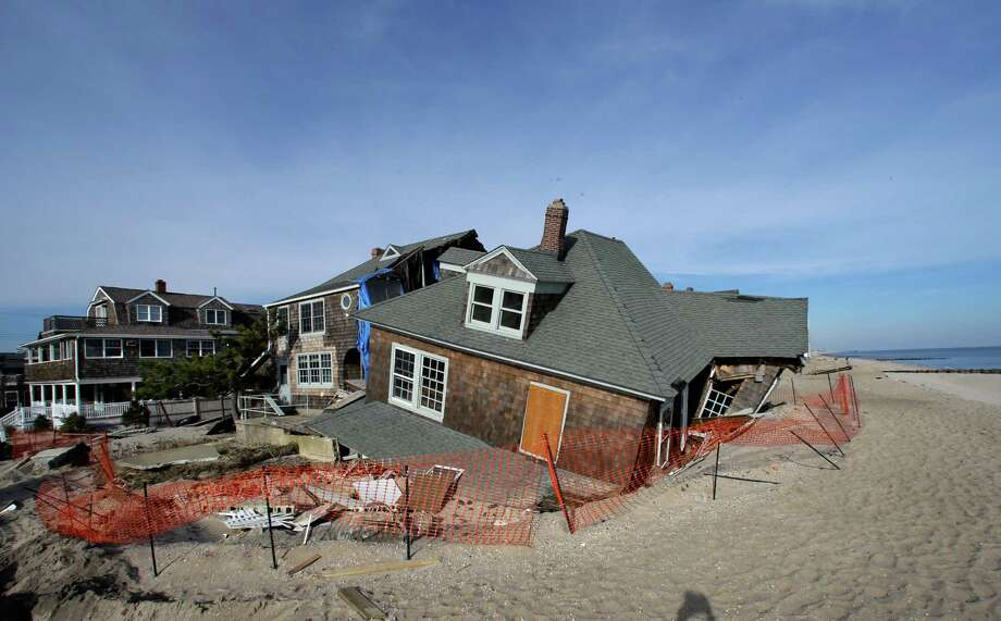 This Jan. 3, 2013 photo shows a beach front home that was severely damaged by Superstorm Sandy resting in the sand in Bay Head, N.J., Thursday, Jan. 3, 2013.  House conservatives opposed to more deficit spending chip away at a $50.7 billion Superstorm Sandy aid package by seeking spending cuts in other programs to pay for recovery efforts and stripping money for projects they say are unrelated to the Oct. 29 storm.   (AP Photo/Mel Evans) Photo: Mel Evans