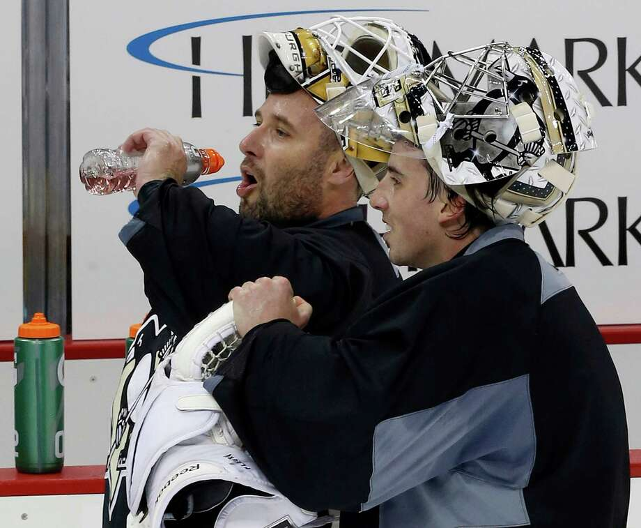 Pittsburgh Penguins goalies Marc-Andre Fleury, right, and newly acquired backup Tomas Vokoun take a break during an NHL hockey practice at the Consol Energy Center in Pittsburgh Monday, Jan. 14, 2013. (AP Photo/Gene J. Puskar) Photo: Gene J. Puskar