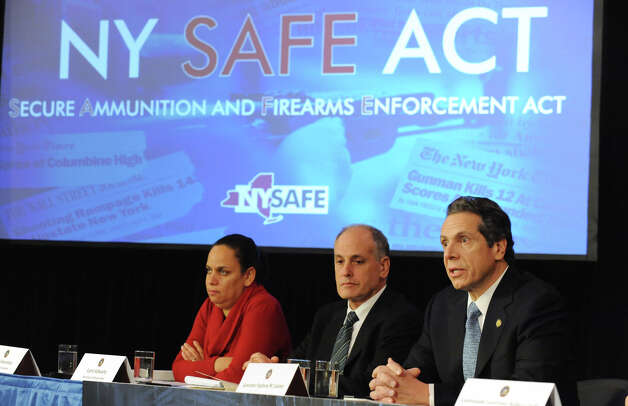 Governor Andrew Cuomo, right, holds a press conference at the Capitol about a bill to broaden the state's definition of banned assault weapons, increase penalties for those convicted of gun crimes and create a statewide registry of assault rifles on Monday Jan. 14, 2013 in Albany, N.Y. Sitting next to Cuomo is Mylan Denerstein, Counsel to the Governor, left, and Larry Schwartz, Secretary to the Governor. (Lori Van Buren / Times Union) Photo: Lori Van Buren