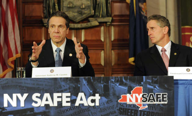 Governor Andrew Cuomo, left, holds a press conference at the Capitol about a bill to broaden the state's definition of banned assault weapons, increase penalties for those convicted of gun crimes and create a statewide registry of assault rifles on Monday Jan. 14, 2013 in Albany, N.Y. Lt. Gov. Robert Duffy looks on at right.(Lori Van Buren / Times Union) Photo: Lori Van Buren